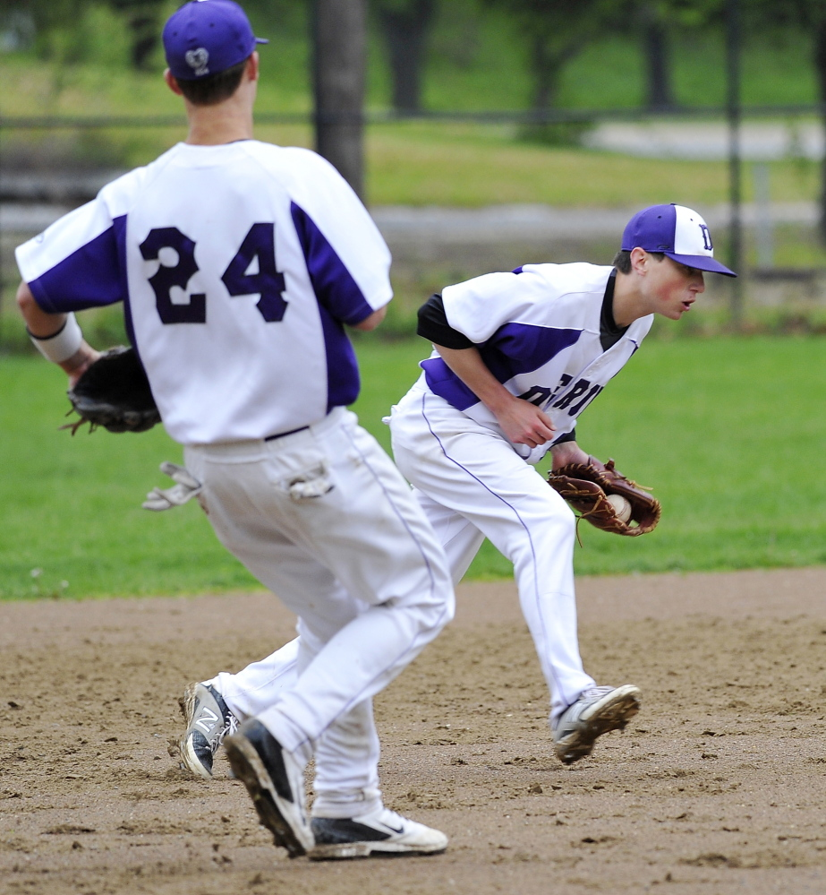 PORTLAND, ME - MAY 27: Deering third baseman, #24, William Barlock watches as shortstop, #7, Nicholas Bevilacua gloves a hard hit grounder and throws the batter out as Portland HS hosts Deering in high school baseball action at Deering Oaks.