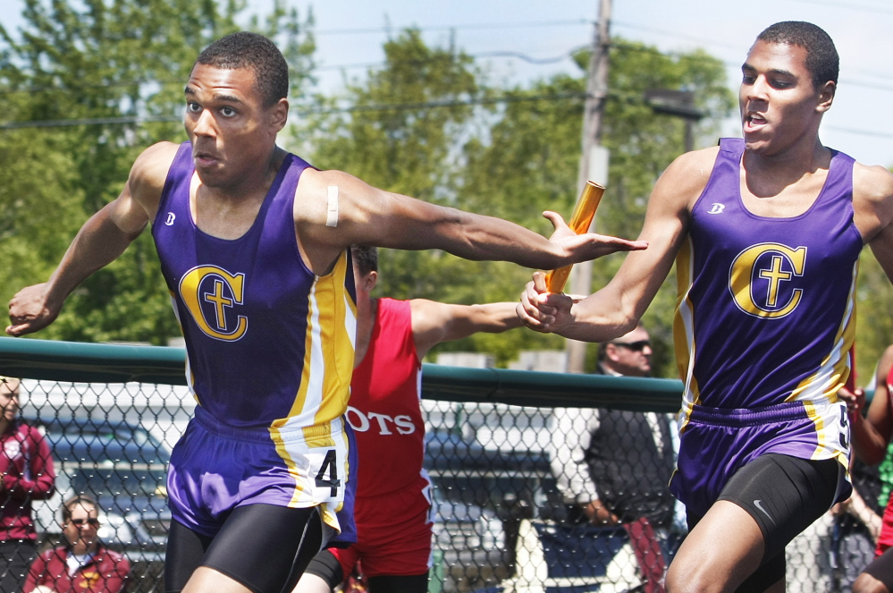 Elijah Yeboah, right, of Cheverus hands the baton to his twin brother, Isaac, in the 400-meter relay at the SMAA meet. The brothers helped Cheverus win both the 400 and 1,600 relays, and Isaac also swept the two hurdle races as the Stags won the team title.