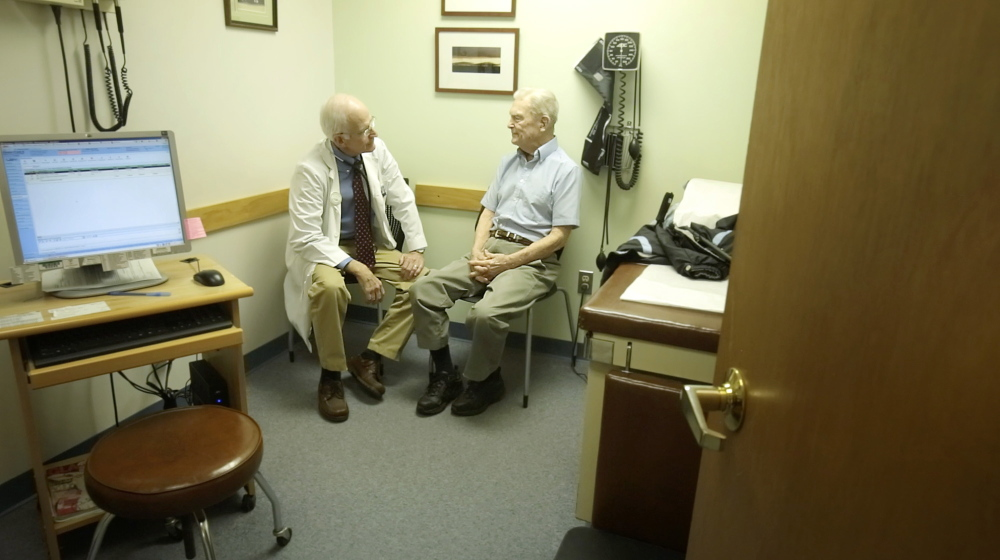 """Dr. William Medd talks with patient Frank Floster at Medd's primary care practice in Norway. Medd, 71, recently recovered from heart surgery and worries about who take his place when he retires. """"You don't want to feel like you're abandoning your patients,"""" he said."""