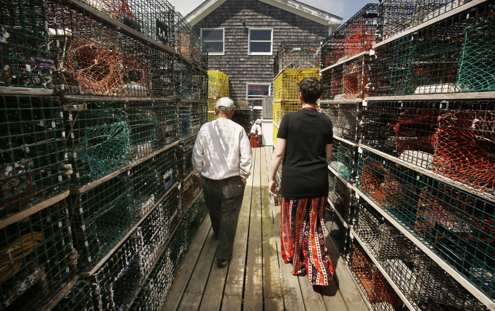 """Jennifer Desmond walks past lobster traps with Harold """"Sonny"""" Warren on the dock at his Vinalhaven home last month. Desmond has a recreational lobster license and Warren, who is also a Korean War veteran, helps her haul her traps. """"He's my sternman,"""" she said."""