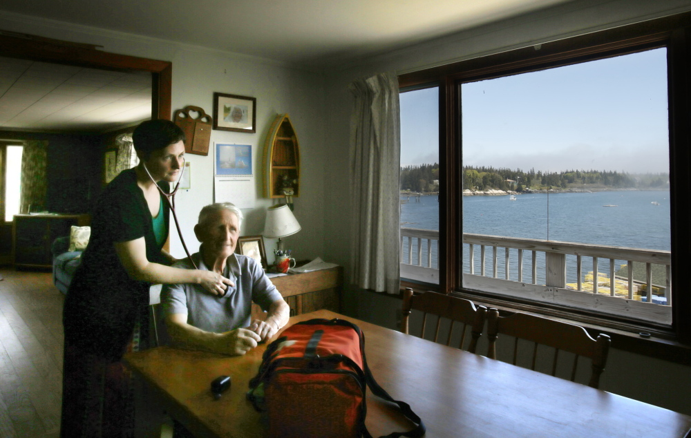 """Nurse practitioner Jennifer Desmond checks on Harold """"Sonny"""" Warren at his home on Vinalhaven. Desmond """"is the best thing to ever happen to Vinalhaven,"""" the 86-year-old lobsterman said. """"She's stuck with us night and day. Six of the other doctors left."""" Photos by Gregory Rec/Staff Photographer"""