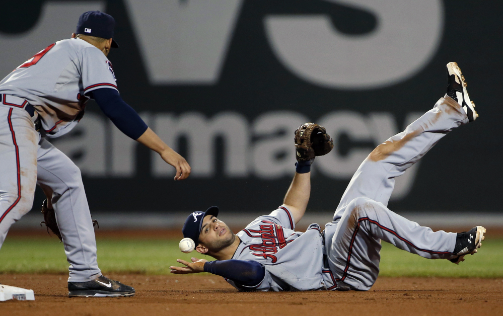 Atlanta Braves second baseman Tommy La Stella bobbles an infield hit by Boston's Dustin Pedroia as shortstop Andrelton Simmons waits at second base for the ball during the eighth inning at Fenway Park on Thursday, May 29, 2014. Boston won 4-3 thanks to defensive miscues by Atlanta.