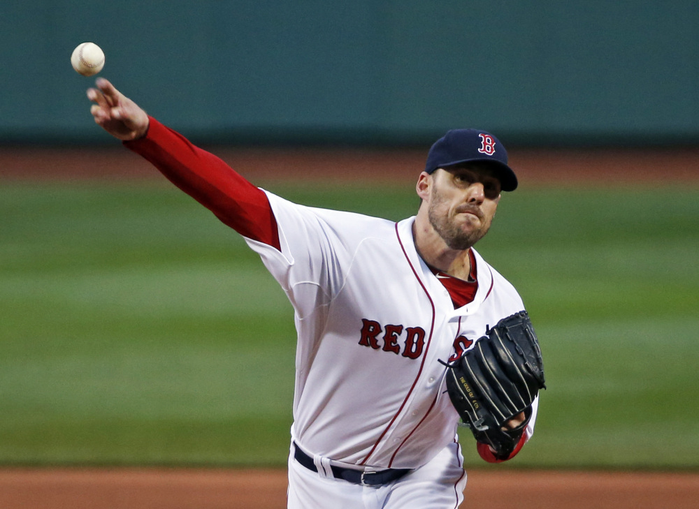 Boston Red Sox starting pitcher John Lackey delivers to the Atlanta Braves in the first inning of a baseball game at Fenway Park in Boston, Wednesday, May 28, 2014. The Associated Press/Elise Amendola