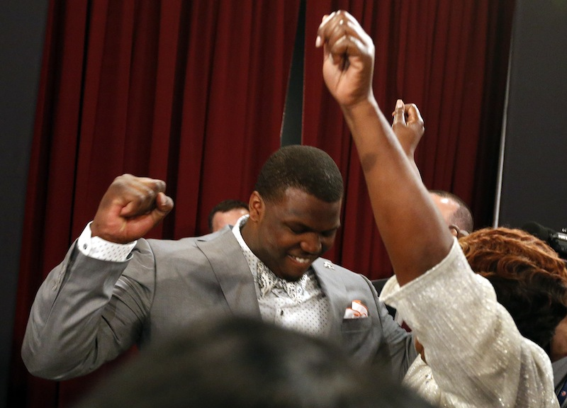Greg Robinson, from Auburn, celebrates after being selected second overall in the first round of the NFL football draft by the St. Louis Rams on Thursday.