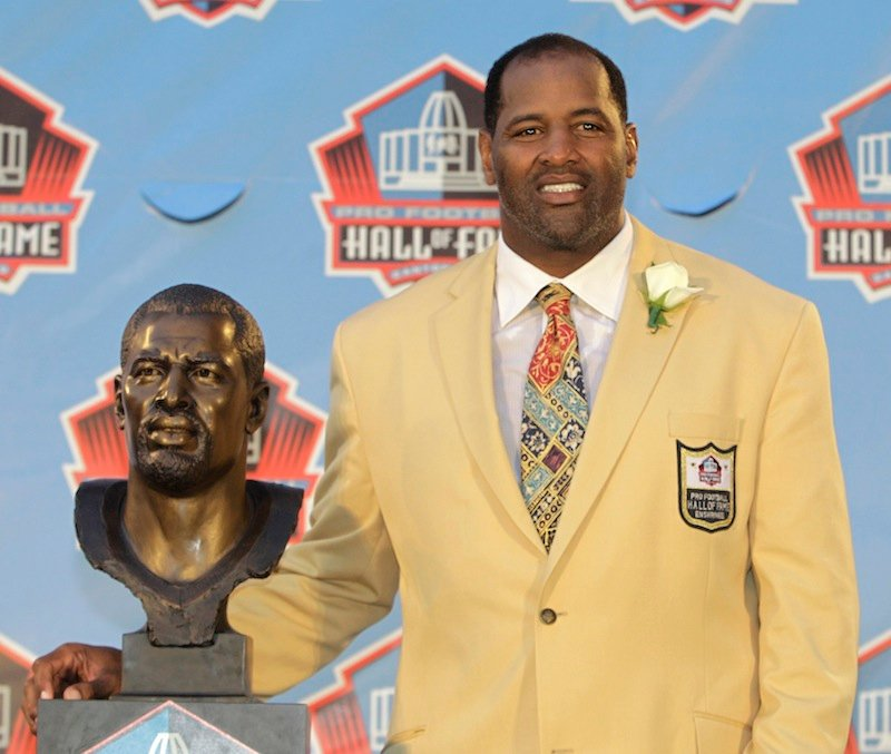 In this August 2011 file photo, Richard Dent poses with a bust of himself during induction ceremonies at the Pro Football Hall of Fame in Canton, Ohio. A group of retired NFL players says in a lawsuit that the league illegally supplied them with risky painkillers that numbed their injuries and led to medical complications.