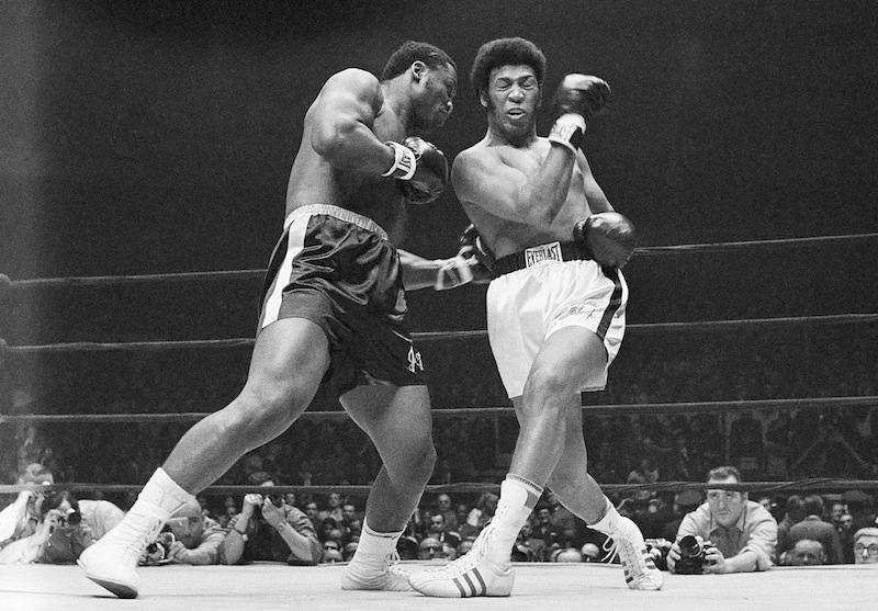 In this Feb. 16, 1970, file photo, Joe Frazier connects to the body of Jimmy Ellis who misses with a right during the first round of their heavyweight title bout at Madison Square Garden in New York. boxing full length left punch press referee ringside