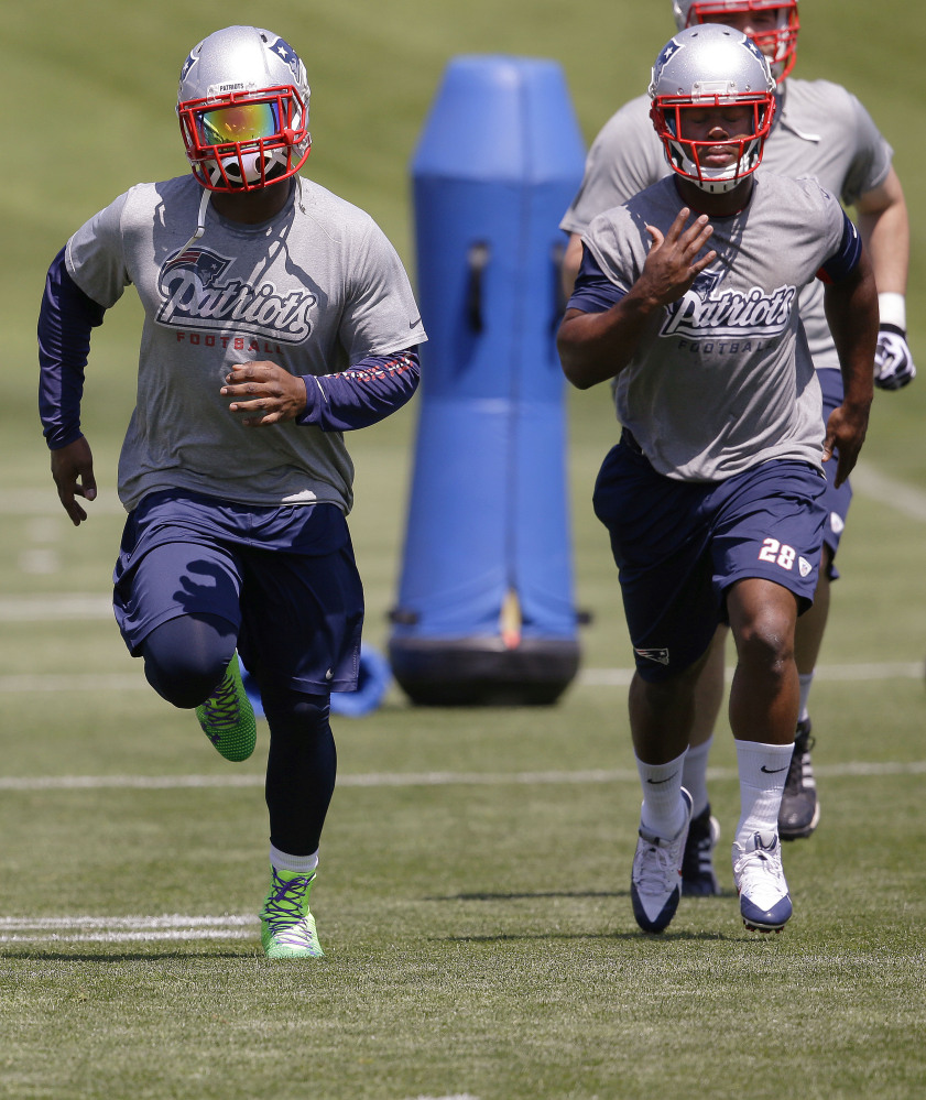 New England Patriots rookie running back James White (28) and running back Stevan Ridley run while stretching  during an organized team activity at the NFL football team's facility Friday, May 30, 2014 in Foxborough, Mass. The Associated Press/Stephan Savoia