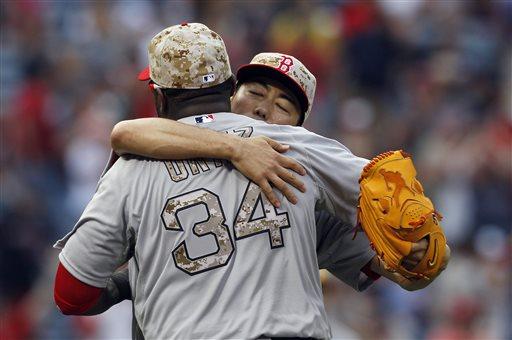 Red Sox pitcher Koji Uehara hugs David Ortiz after Boston defeated the Braves 8-6 Monday in Atlanta.