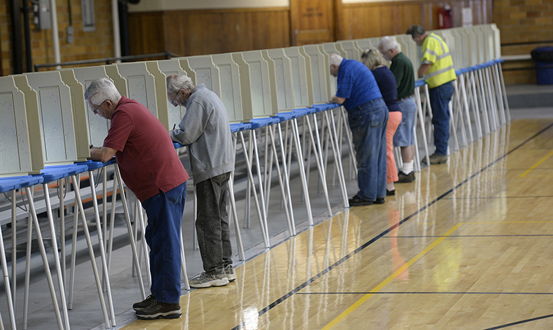 Voters fill out their ballots at the J. Richard Martin Community Center in Biddeford Tuesday. To the far left is Raymond Collard of Biddeford. Shawn Patrick Ouellette/Staff Photographer