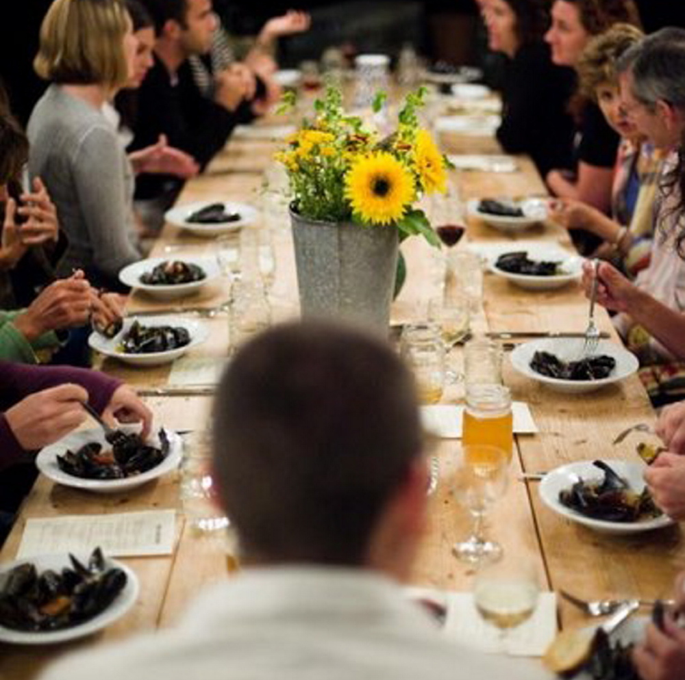 Diners at Salt Water Farm's events share a communal table, fresh farmed and foraged food, and ocean views.