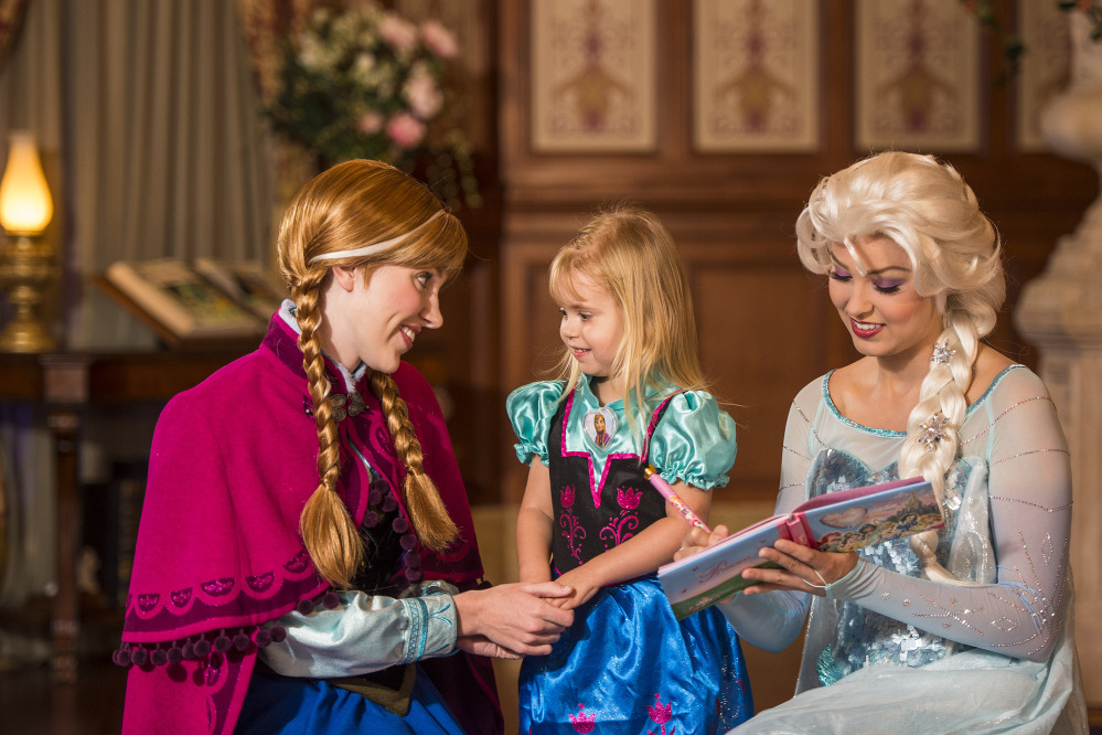 """Disney characters playing princesses from the animated movie """"Frozen,"""" Anna, left, and her sister Elsa, right, talk with a young fan at Walt Disney World Resort in Lake Buena Vista, Fla. Wait times to meet the sisters stretches for hours and reservations are snapped up quickly. The Associated Press"""