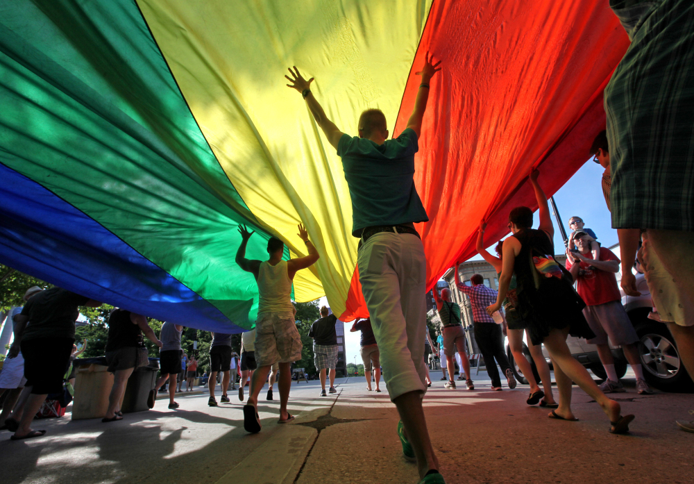 Supporters of a U.S. Supreme Court ruling  that overturned the federal Defense of Marriage Act carry a large rainbow flag during a parade around the Wisconsin State Capitol in Madison, Wis. A federal judge struck down Wisconsin's ban on same-sex marriage Friday, ruling it unconstitutional. The Associated Press/Wisconsin State Journal