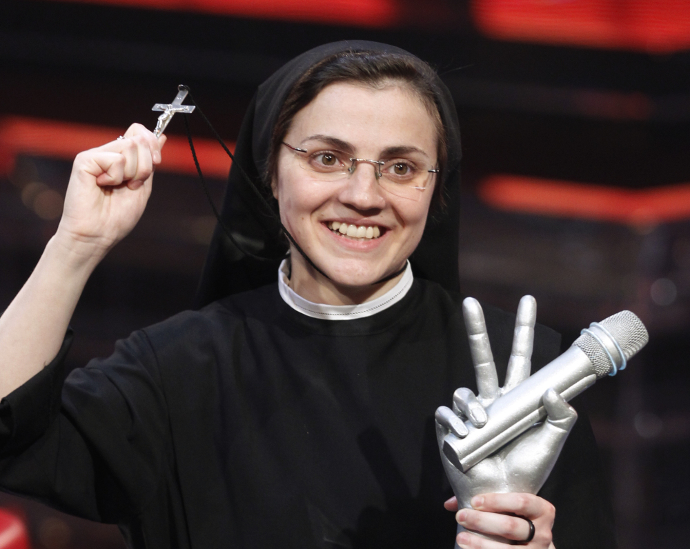 """Sister Cristina Scuccia poses with the trophy and holding a cross after winning the final of the Italian version of the TV talent show """"The Voice"""" in Milan, Italy, on Friday. The Associated Press"""