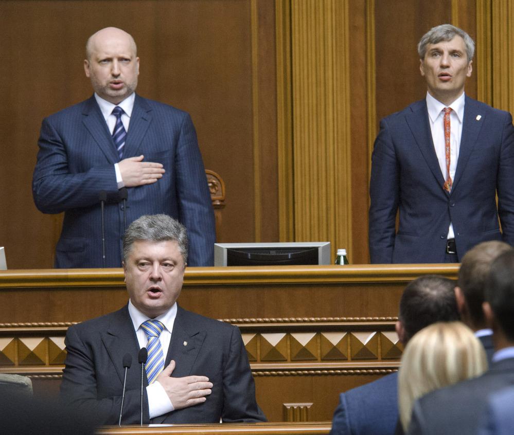 Ukrainian President-elect Petro Poroshenko, foreground, sings the national anthem during his inauguration ceremony in Kiev, Ukraine, on Saturday. The Associated Press