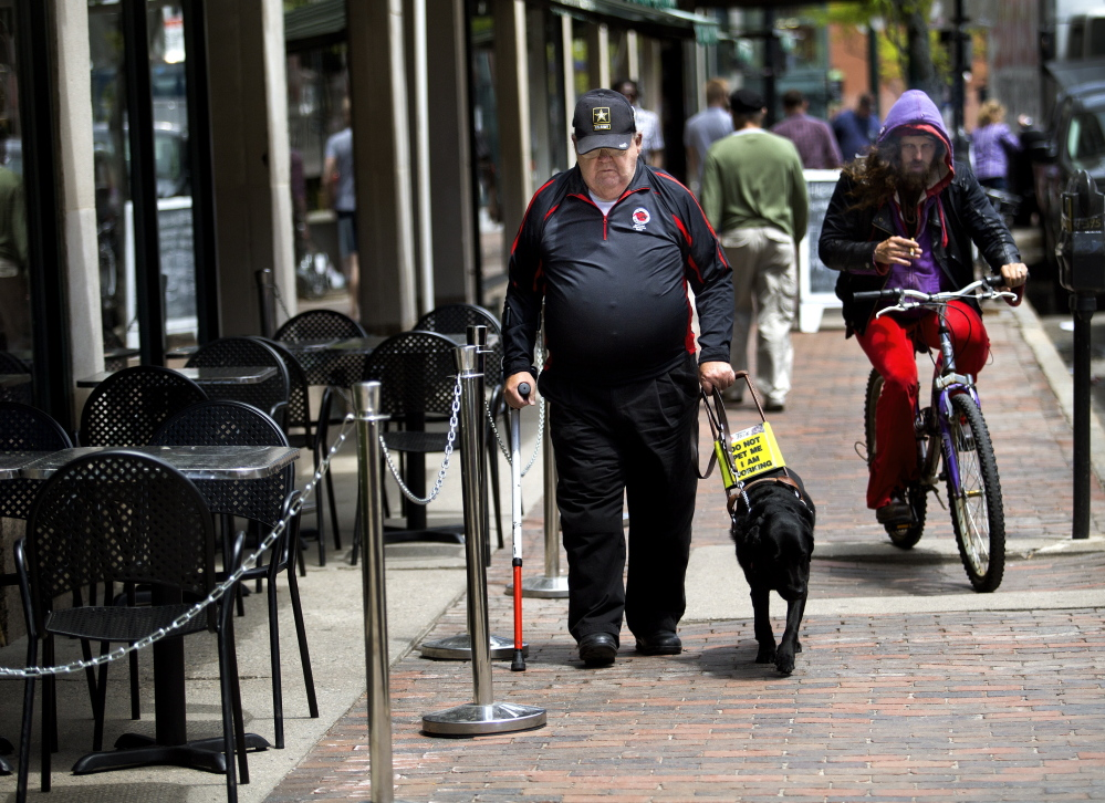 Bud Buzzell, who is visually impaired, walks with his guide dog outside Congress Bar & Grill, which has outdoor seating that appears to leave 4 feet of sidewalk space as required. Gabe Souza/Staff Photographer