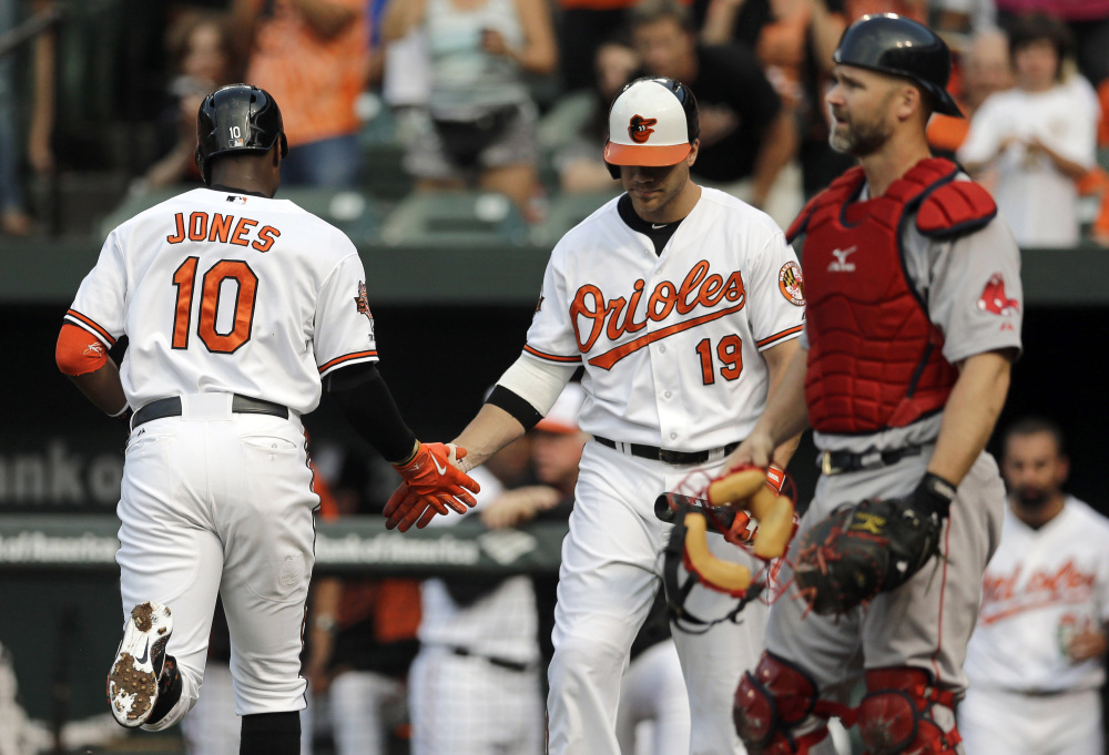 The Associated Press/Patrick Semansky Baltimore Orioles' Adam Jones, left, is greeted by teammate Chris Davis in front of Boston Red Sox catcher David Ross, right, after Jones hit a solo home run in the first inning.