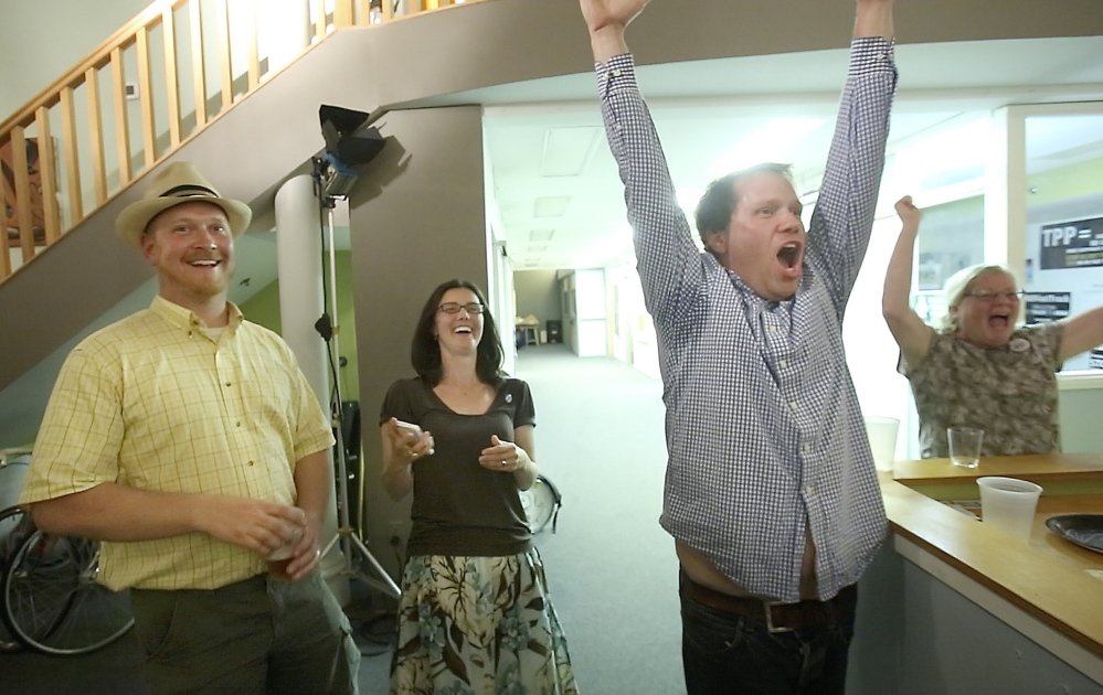 """Volunteer Chris Moore, right, celebrates the win by the Yes on 1 campaign in Portland on Tuesday night, joined by his wife, Bree LaCasse, center, and City Councilor David Marshall. """"We hope city officials heard us loud and clear,"""" LaCasse said. Gregory Rec/Staff Photographer"""