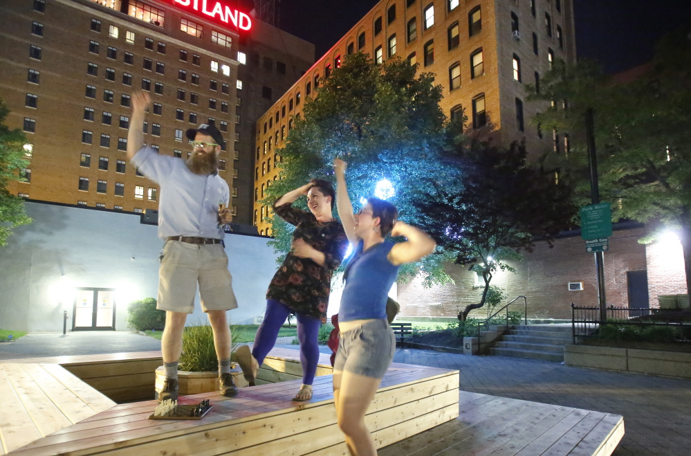 """Yes on 1 campaign volunteers Asher Platts, left, and Becky Wartell, right, and Lauren Besanko, a campaign staffer, dance in Congress Square Plaza on Tuesday. The """"very close vote"""" blocked the sale of the park, but also had far broader implications for city-owned land. Gregory Rec/Staff Photographer"""