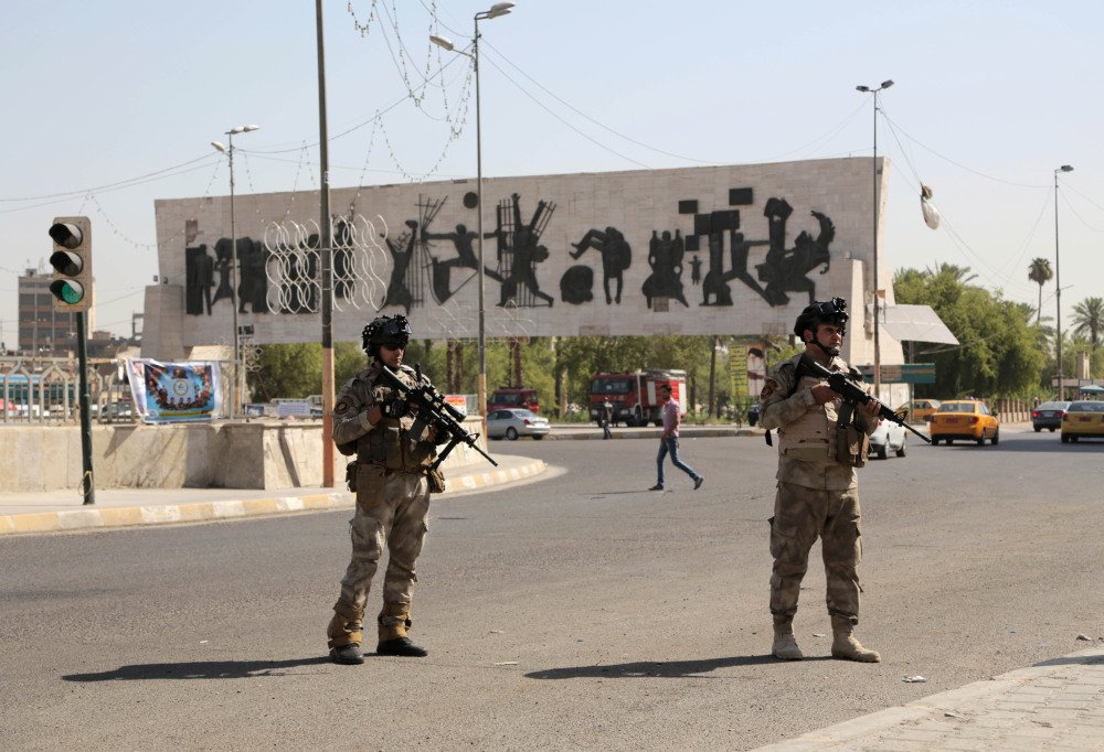 Iraqi army soldiers stand guard at Tahrir Square in Baghdad on Monday. Sunni militants captured a key northern Iraqi town along the highway to Syria early on Monday, compounding the woes of Iraq's Shiite-led government a week after it lost a vast swath of territory to the insurgents in the country's north.