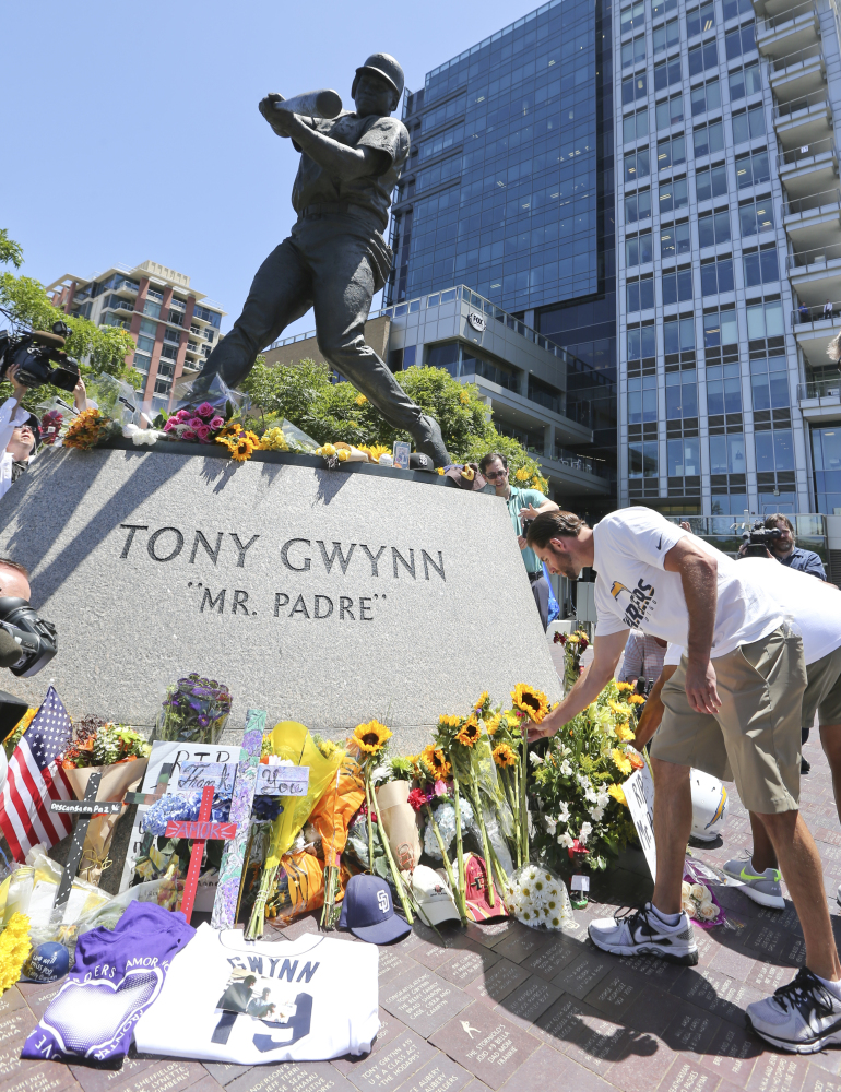 "Members of the San Diego Chargers place flowers at the base of the Tony Gwynn ""Mr. Padre"" statue, Monday, June 16, 2014, in San Diego. Gwynn, an eight time National League batting champion with the San Diego Padres and a member of Baseball Hall of Fame, died Monday from cancer. He was 54."