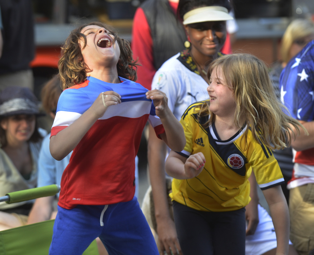 Portland community groups organized a World Cup viewing party Monday in Portland's Congress Square Plaza. Diego Schair-Cardona, left, and his friend Sloan Gardner, both from Portland, react to the game's first goal by the United States.