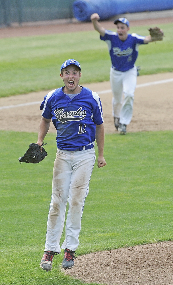 Sacopee Valley starting pitcher Anthony Haskell celebrates along with third baseman Kyle Jordan, background, after the Hawks beat St. Dominic 4-2 to win the Western C regional baseball title Tuesday at St. Joseph's College in Standish.