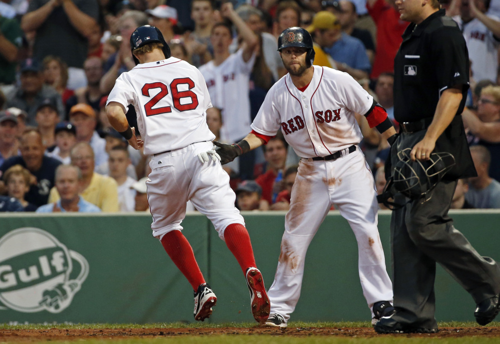 Boston Red Sox's Brock Holt (26) is congratulated by teammate Dustin Pedroia as he scores on a sacrifice fly by Xander Bogaerts in the third inning.