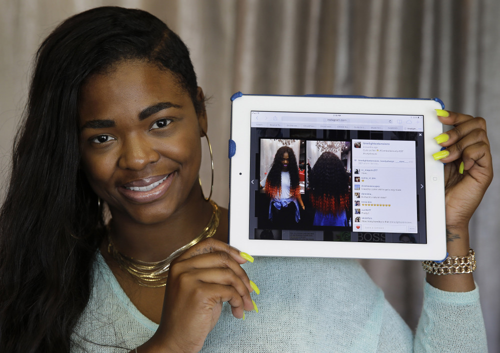 Miranda Jade Plater, owner of Limelight Extensions, poses with a tablet showing an Instagram photo of her wearing long, black curly hair extensions with the ends dyed bright orange at her salon in Farmington Hills, Mich., on Wednesday. That photo alone has generated about $10,000 in sales.