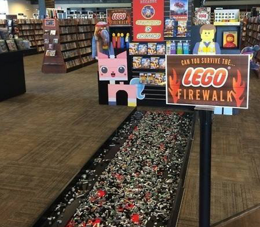 """Customers at Bull Moose in South Portland earned a discount on """"The Lego Movie"""" DVD if they could scoot barefoot across the """"fire walk"""" of Lego pieces Tuesday."""