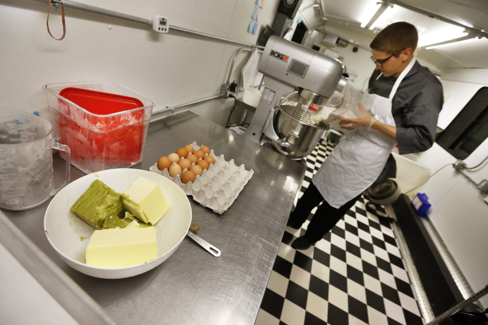 """Chef Alex Tretter prepares a batter for peanut butter and jelly cups, with green cannabis-infused """"canna butter"""" in a bowl at left, at Sweet Grass Kitchen, a gourmet marijuana edibles bakery that sells its confections to retail outlets, in Denver."""