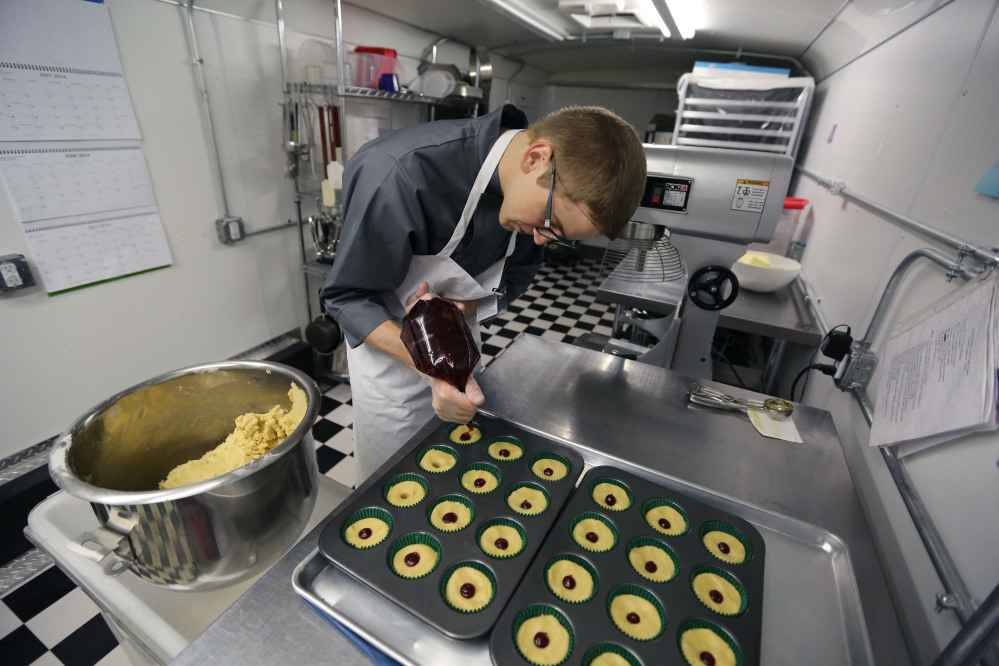 Chef Alex Tretter adds strawberry jam to cannabis-infused peanut butter and jelly cups before baking them at Sweet Grass Kitchen, a gourmet marijuana edibles bakery in Denver.