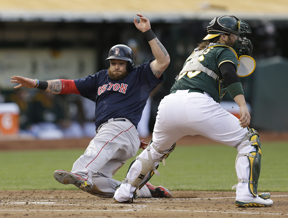 Boston's Jonny Gomes slides past Oakland catcher Derek Norris to score in the second inning Friday in Oakland, Calif. Gomes scored on a single by Jackie Bradley Jr. The Red Sox lost 4-3.