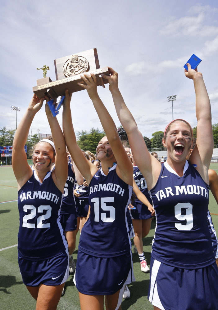 Yarmouth captains Julia Primeau, left, Grace O'Donnell and Abby Belisle Haley, right, hold up the state championship trophy after defeating Cape Elizabeth in the Class B title game on Saturday in Portland.