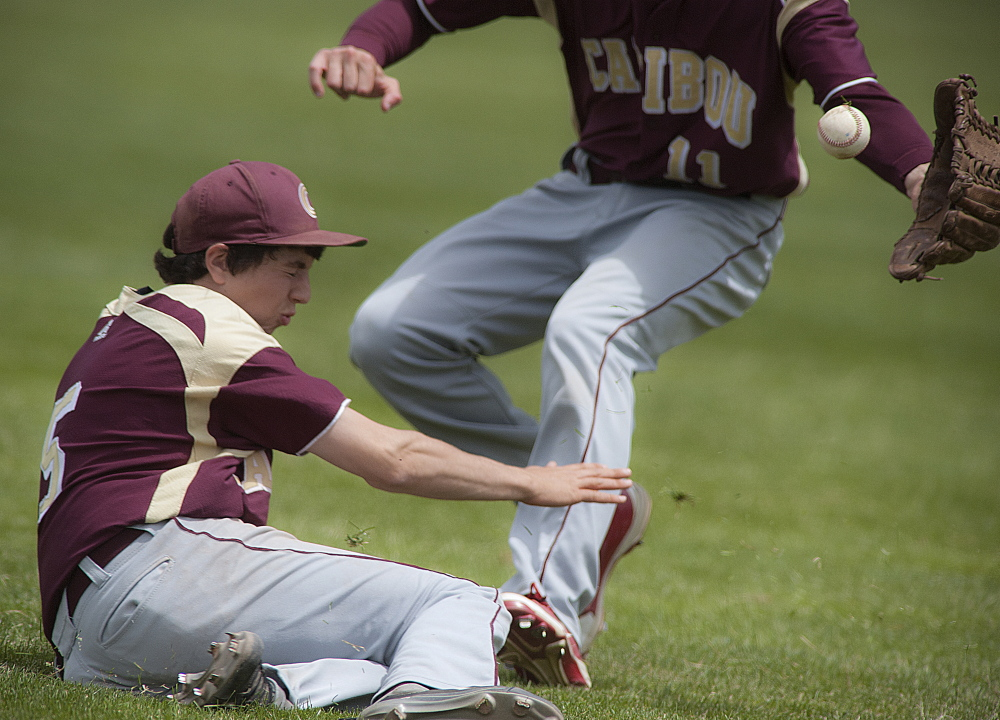 Caribou first baseman Mike Hunter, 5, and right fielder Mason Huck, 11, can't field a ball hit by Greely pinch-hitter Will Bryant in the seventh inning of their state Class B championship game at Mansfield Stadium in Bangor on Saturday.