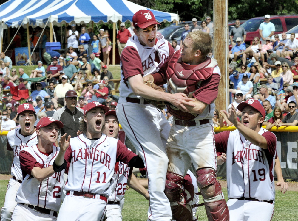 Bangor's pitcher Justin Courtney and catcher Hunter Boyce are joined by teammates as they celebrate their win over Windham for the Class A baseball state championship.