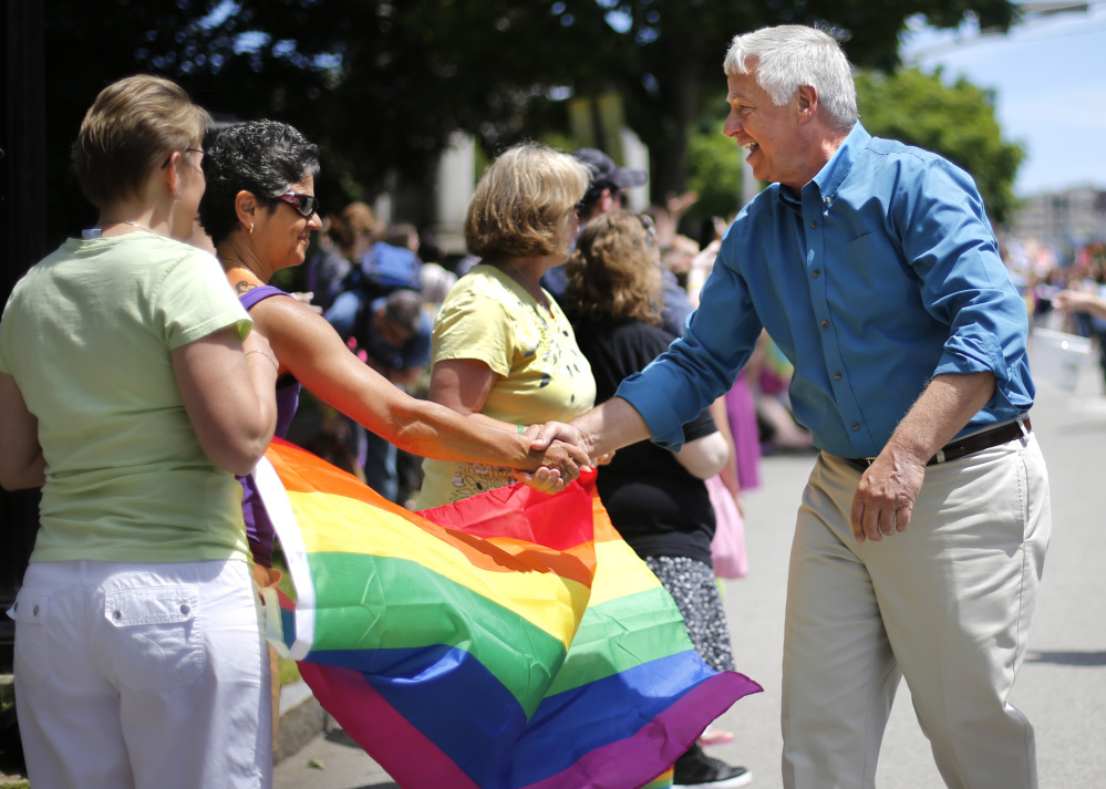 U.S. Rep. Mike Michaud, a Democratic candidate for governor, greets spectators at the Portland Pride Parade on Saturday in Portland.