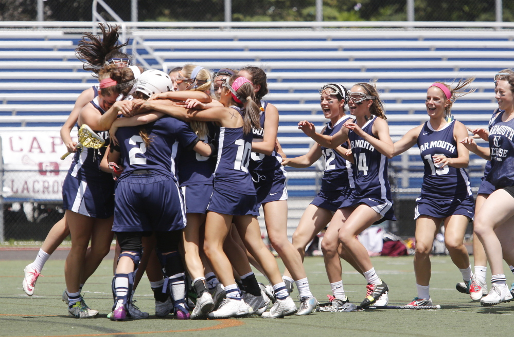Yarmouth teammates mob goalie Mary Kate Gunville after defeating Cape Elizabeth in the Class B State Championship.