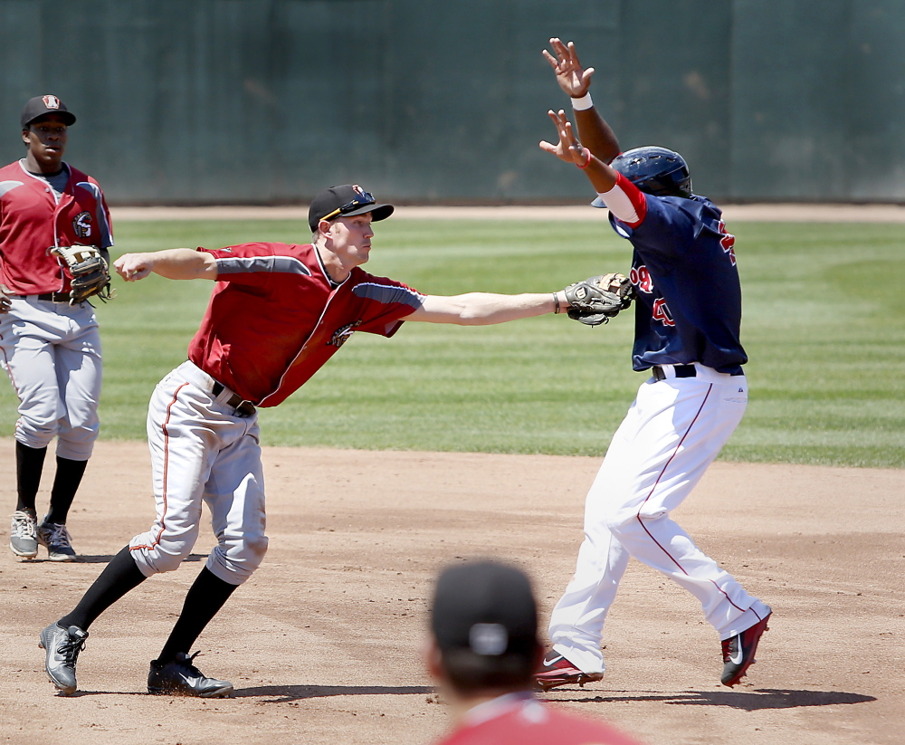 Keury De La Cruz of the Sea Dogs is tagged out on his way to second base by Kelson Brown of the Curve in the first inning of Altoona's 5-4 win at Hadlock Field on Sunday afternoon.