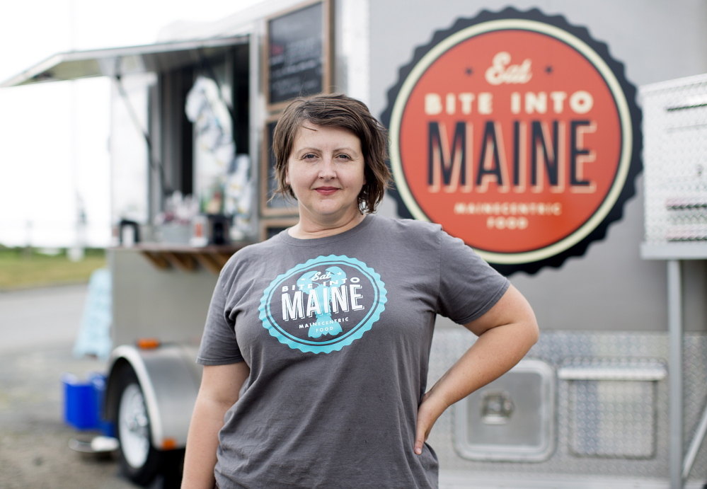 """Sarah Sutton takes a break from selling lobster rolls from her Bite Into Maine food truck at Fort Williams Park on Wednesday. """"We have the best office view ever!"""" she said."""