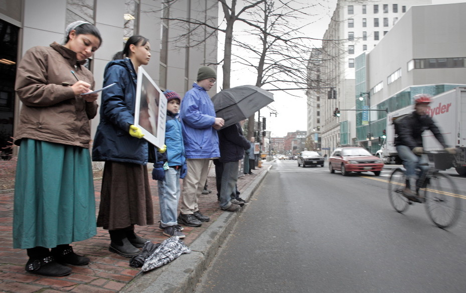 Anti-abortion protesters stand across the street from the Planned Parenthood clinic in Portland on Nov. 22, 2013, the first day they picketed the Congress Street clinic after a 39-foot buffer zone around the clinic took effect.