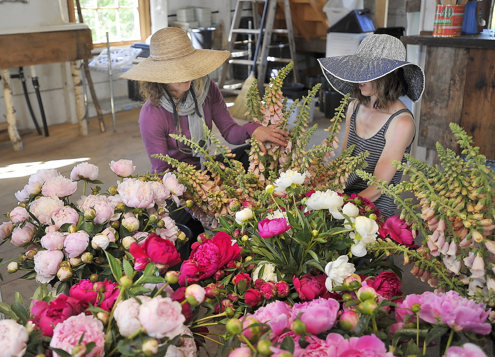 Stacy Brenner, left, owner of Broadturn Farm, and Laura Williams sort and arrange flowers in the farm's flower workshop. The blooms were cut that morning for transportation to buyers.