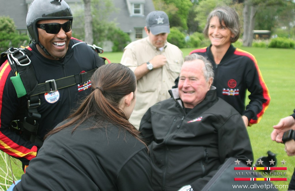 Former President George H.W. Bush is checked by a doctor with the All Veteran Parachute Team after his landing of a parachute jump on his 90th birthday in Kennebunkport on Thursday.