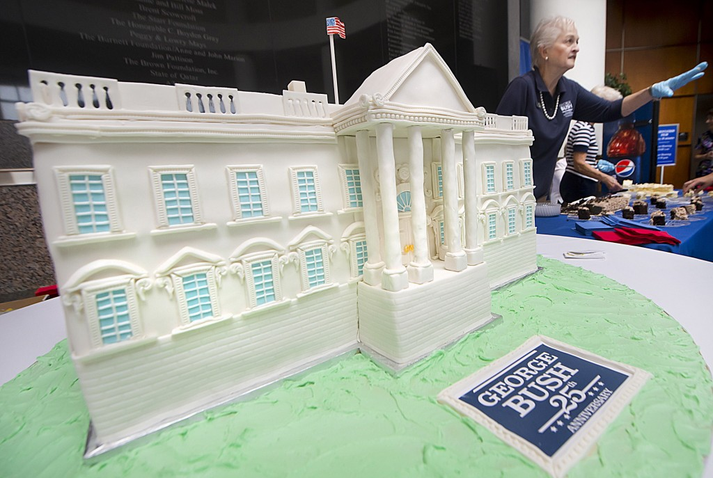 A White House-shaped birthday cake rests on a table as George Bush Presidential Library and Museum docent Sandra Wood passes out free slices of cake at the museum's celebration of Bush's 90th birthday in College Station, Texas, on Thursday.
