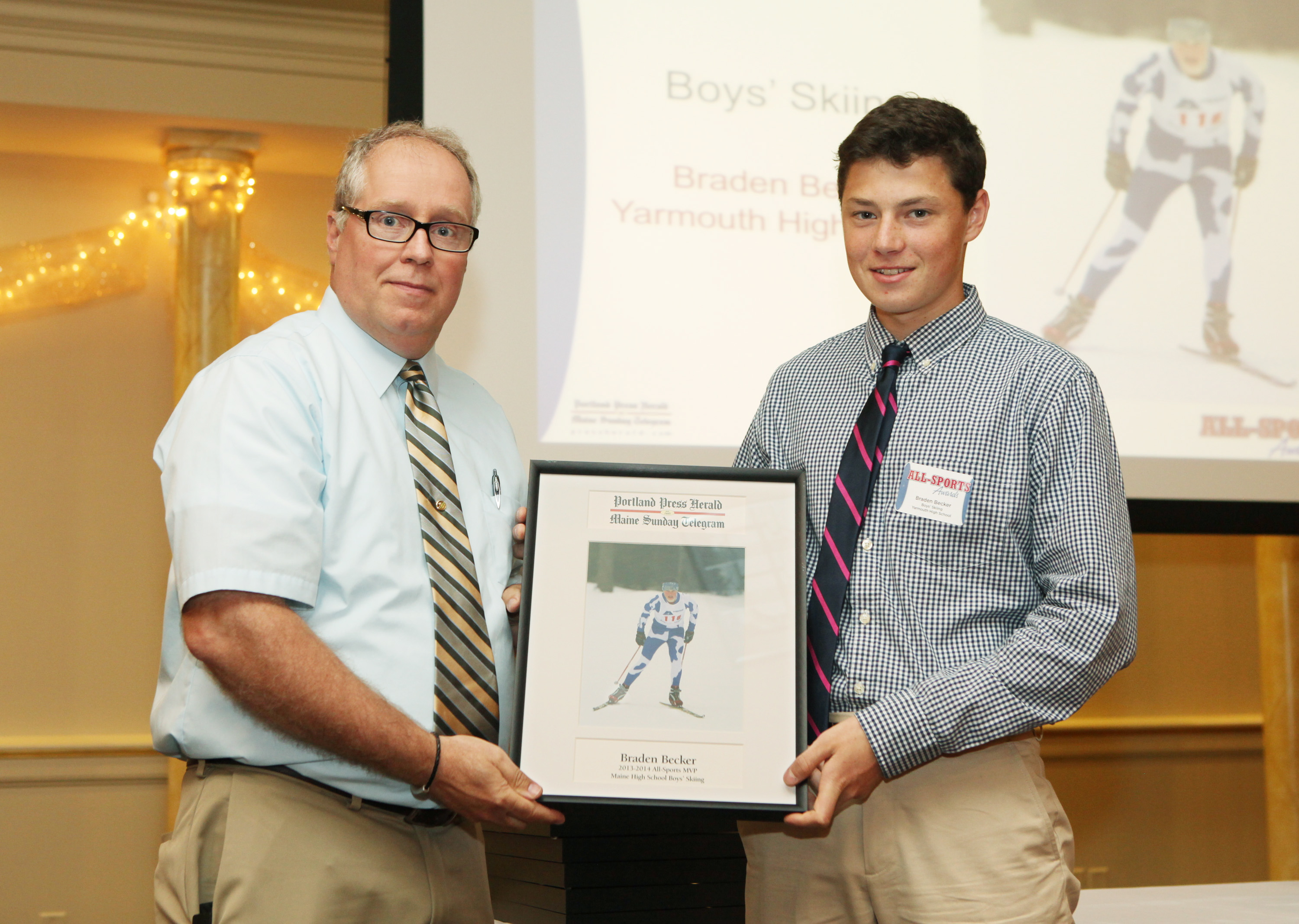 Braden Becker of Yarmouth High School receives an award for skiing from Press Herald sports writer Mike Lowe during the 27th Annual All-Sports Awards Sunday. Joel Page/Staff Photographer