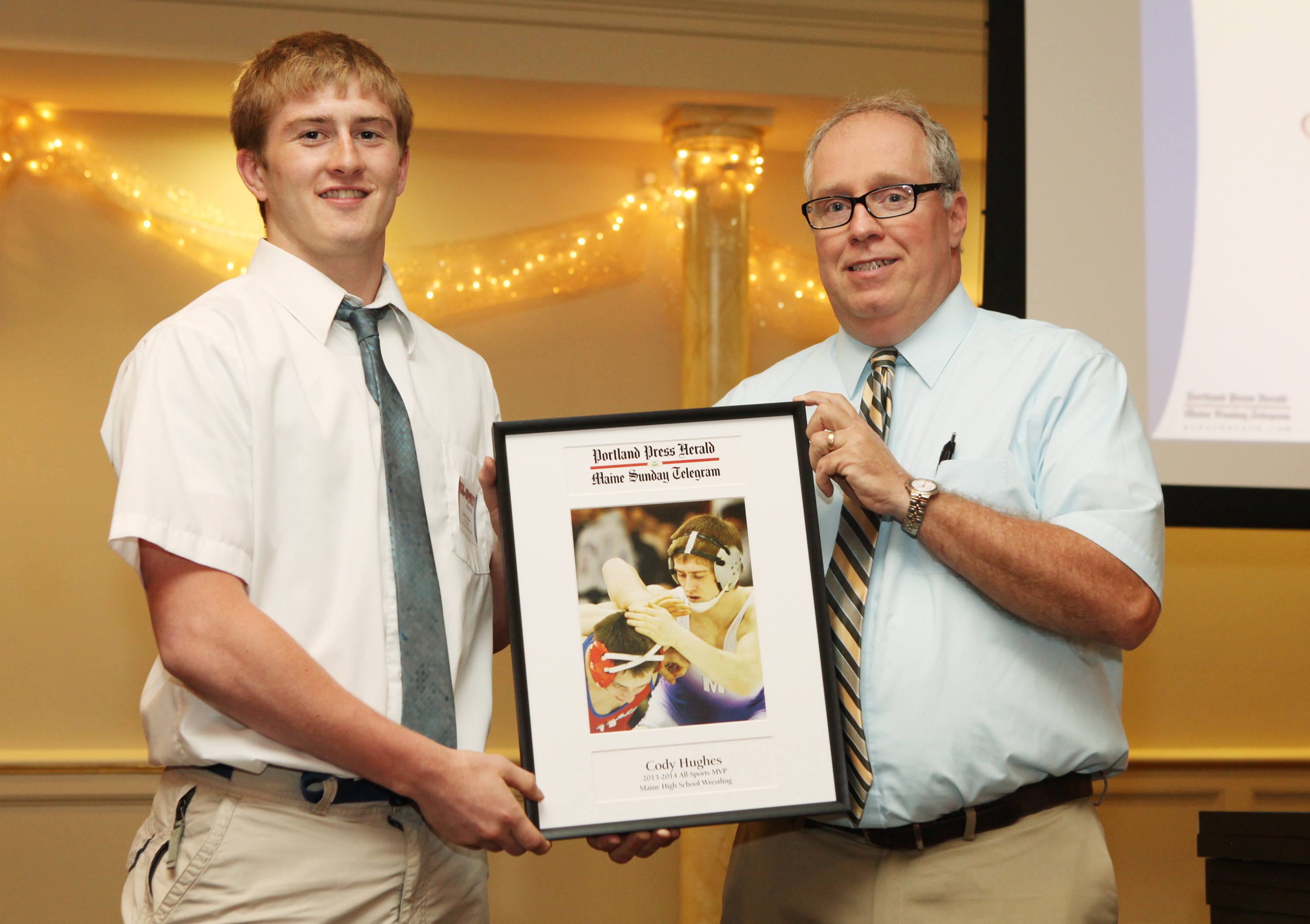 Cody Hughes of Marshwood High School receives an award for wrestling from Press Herald sports writer Mike Lowe during the 27th Annual All-Sports Awards Sunday. Joel Page/Staff Photographer