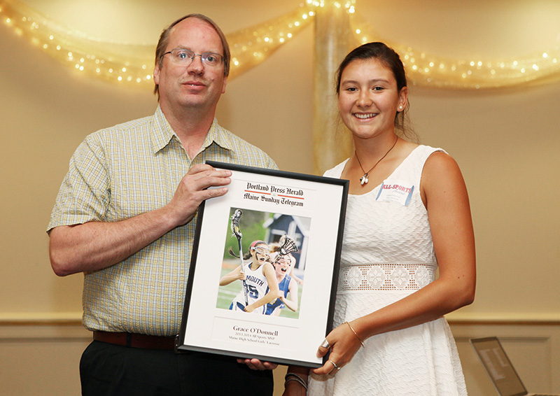 Grace O'Donnell, of Yarmouth High School receives an award for Girl's Lacrosse from Press Herald sports writer Mark Emmert during the 27th Annual All-Sports Awards Sunday. Joel Page/Staff Photographer.