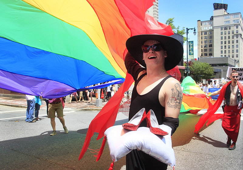 Brett Faulkner carries ruby red slippers as he helps keep control of a giant pride flag as the Portland Pride Parade moves down Congress Street in Portland Saturday. Jill Brady/Staff Photographer