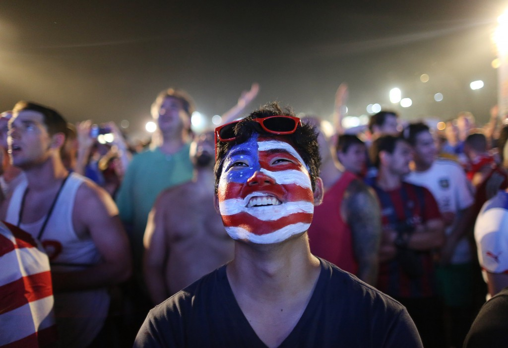 A soccer fan of the U.S. national soccer team watches a live broadcast of the soccer World Cup match between USA and Ghana, inside the FIFA Fan Fest area on Copacabana beach, Rio de Janeiro, Brazil. (AP Photo/Leo Correa)