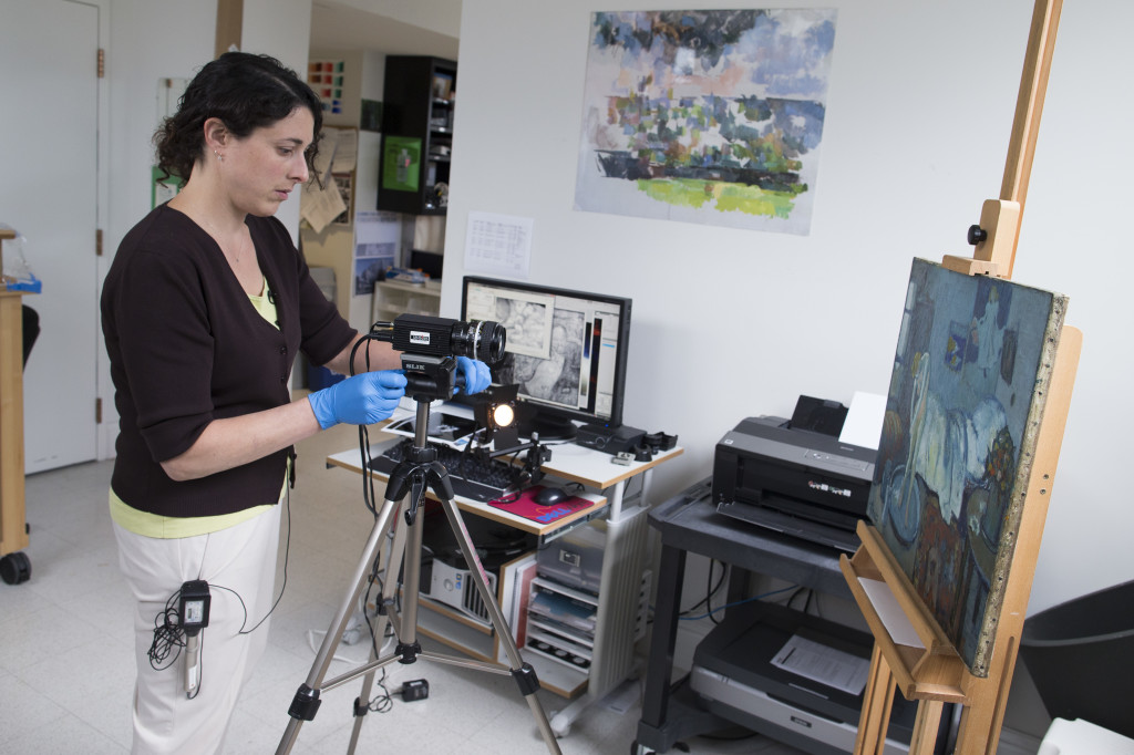 """Patricia Favero, associate conservator at The Phillips Collection, sets up an infared camera to view an image of a man found underneath one of Picasso's first masterpieces, """"The Blue Room,"""" on June 10, 2014 in Washington. The Associated Press"""