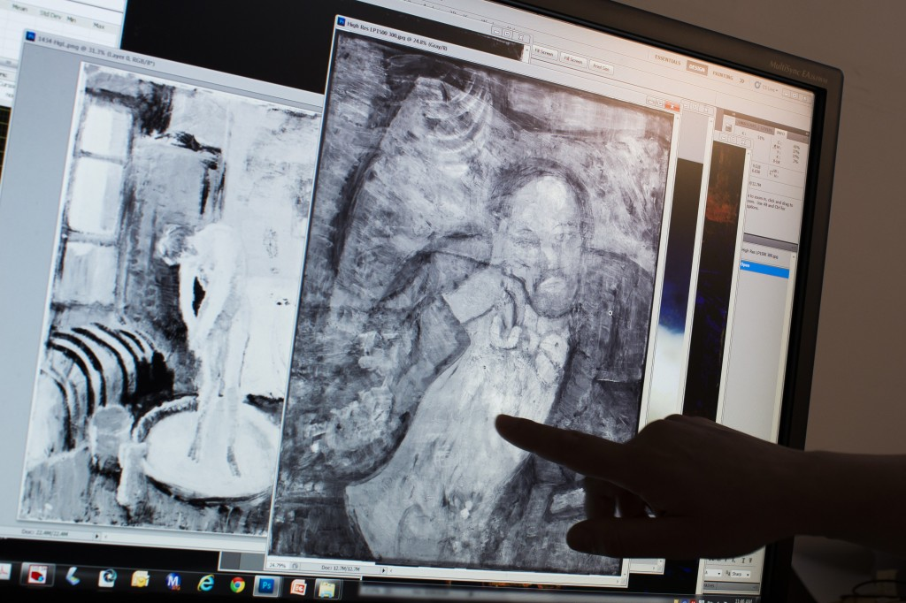 """Patricia Favero, associate conservator at The Phillips Collection, points to an image of a man found underneath one of Picasso's first masterpieces, """"The Blue Room,"""" on  June 10 in Washington.  The Associated Press"""